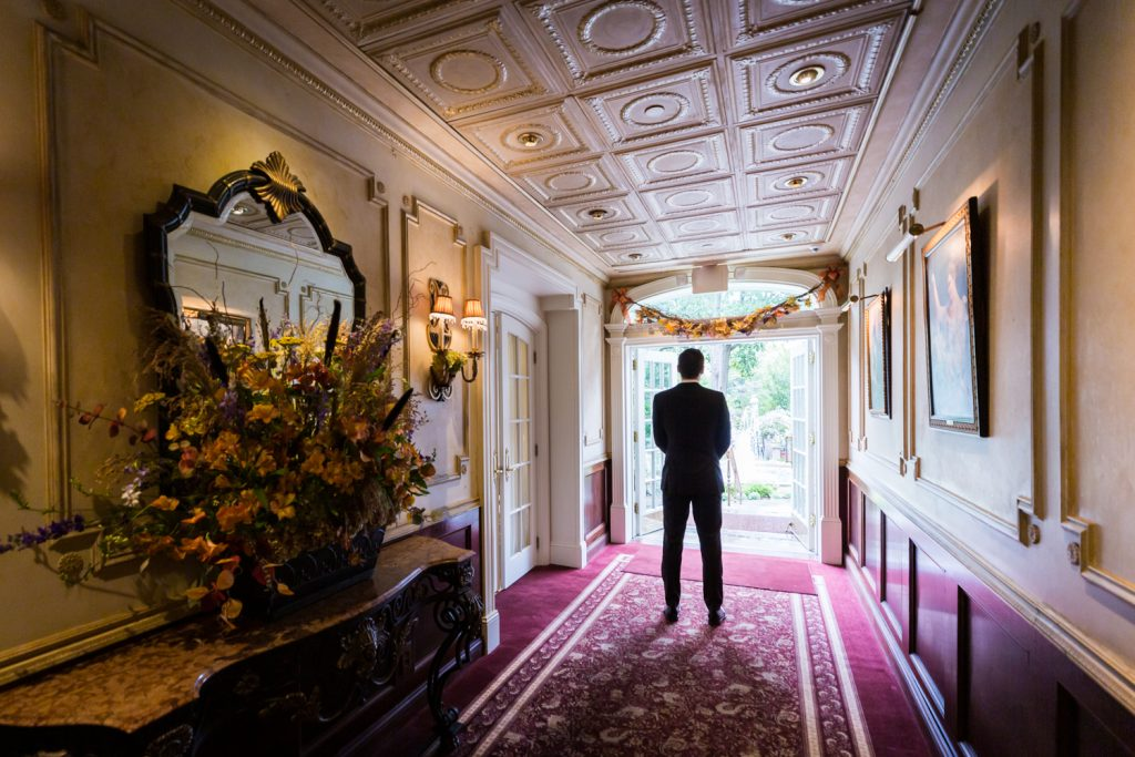 Groom standing at end of hall waiting for first look to begin at a Westbury Manor wedding