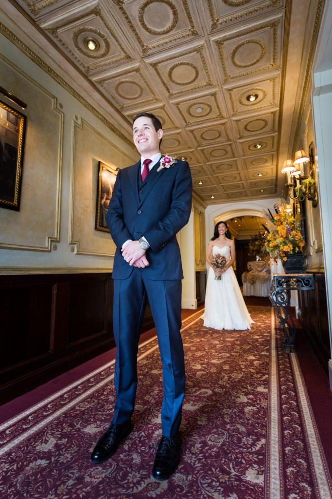 Bride behind groom before first look begins at a Westbury Manor wedding