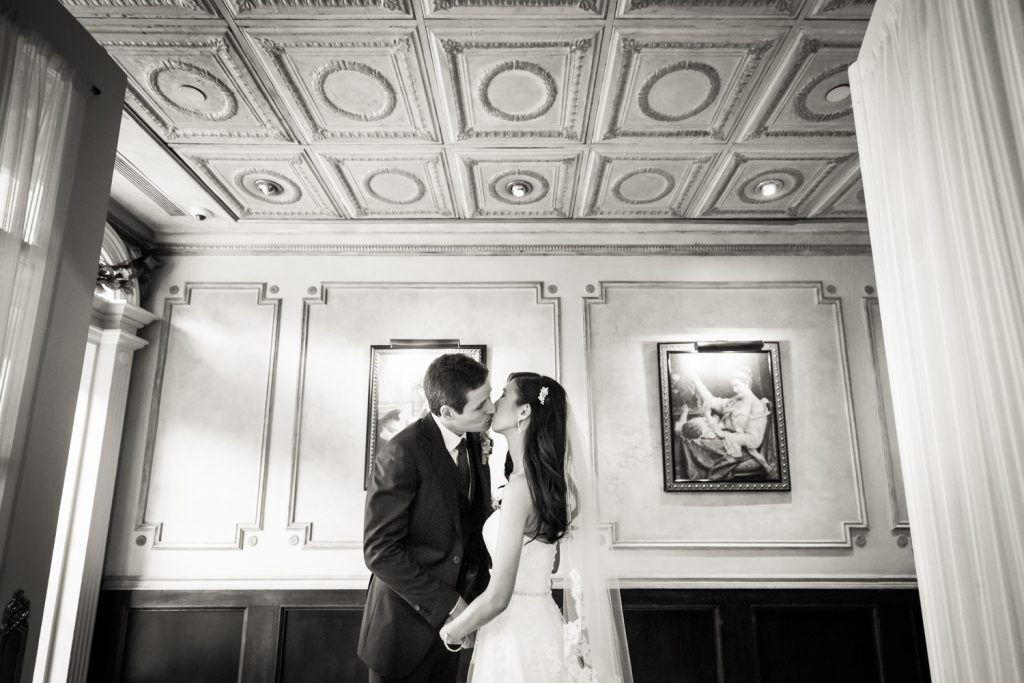 Black and white photo fo bride and groom kissing at a Westbury Manor wedding