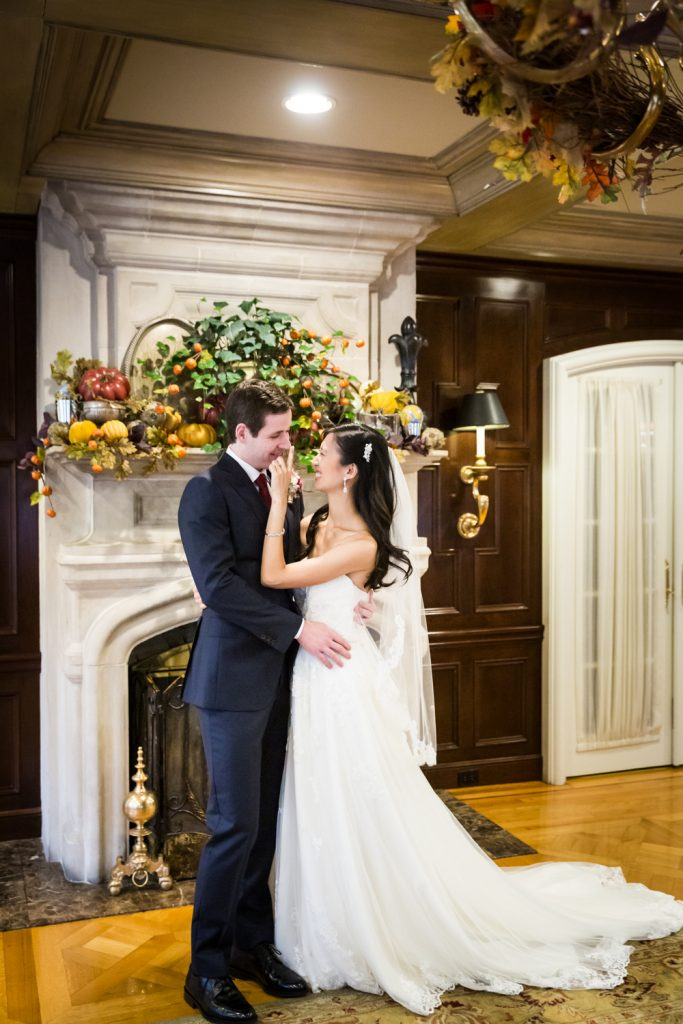 Bride touching groom's nose in front of fireplace
