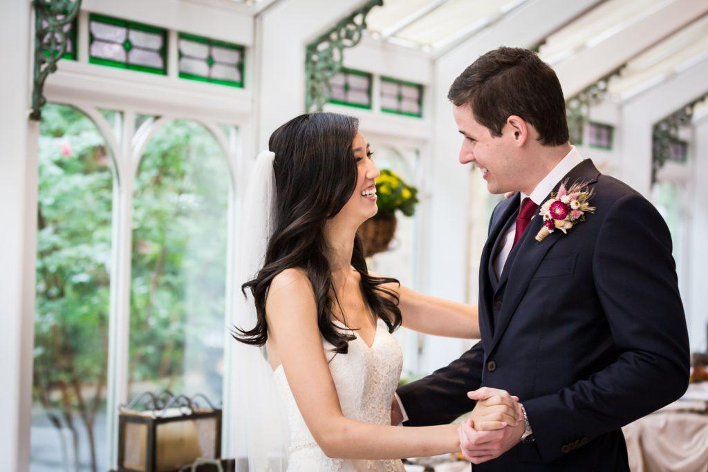 Bride and groom dancing in front of window