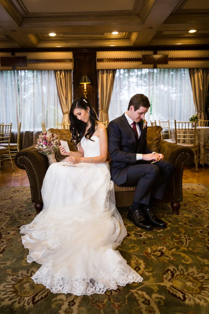 Bride and groom seated with back to each other and reading letters