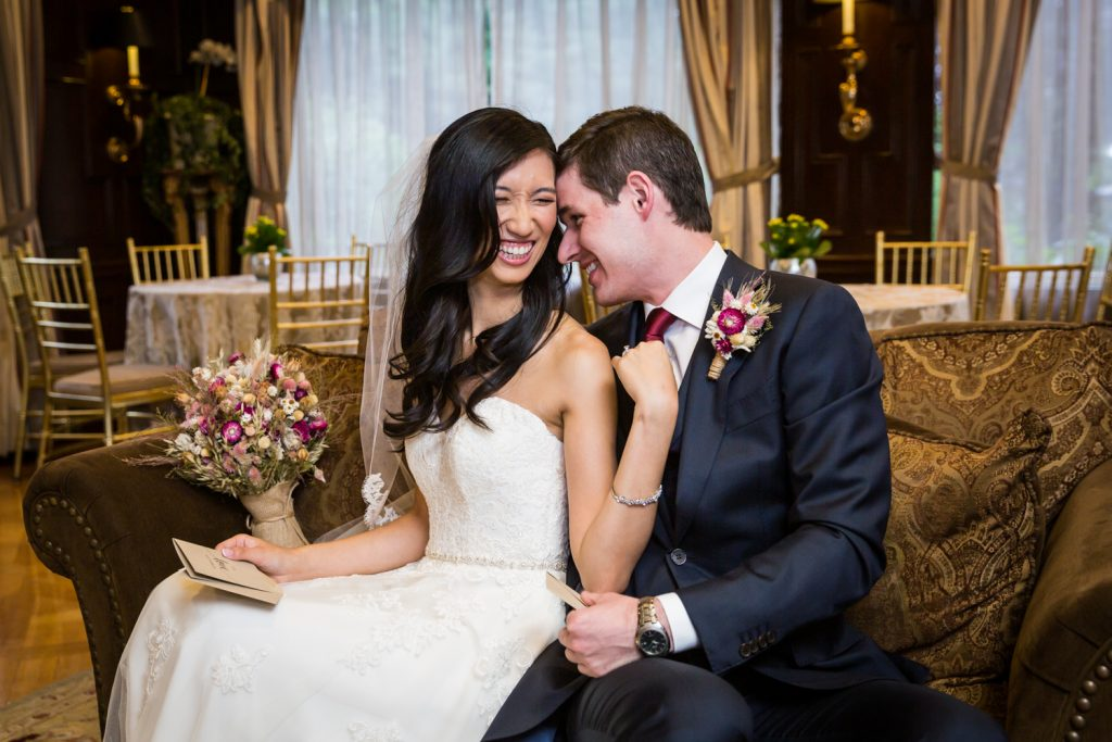 Bride and groom laughing together on couch at a Westbury Manor wedding