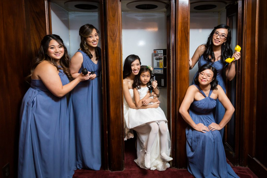Bride and bridesmaids in old fashioned phone booth at a Westbury Manor wedding
