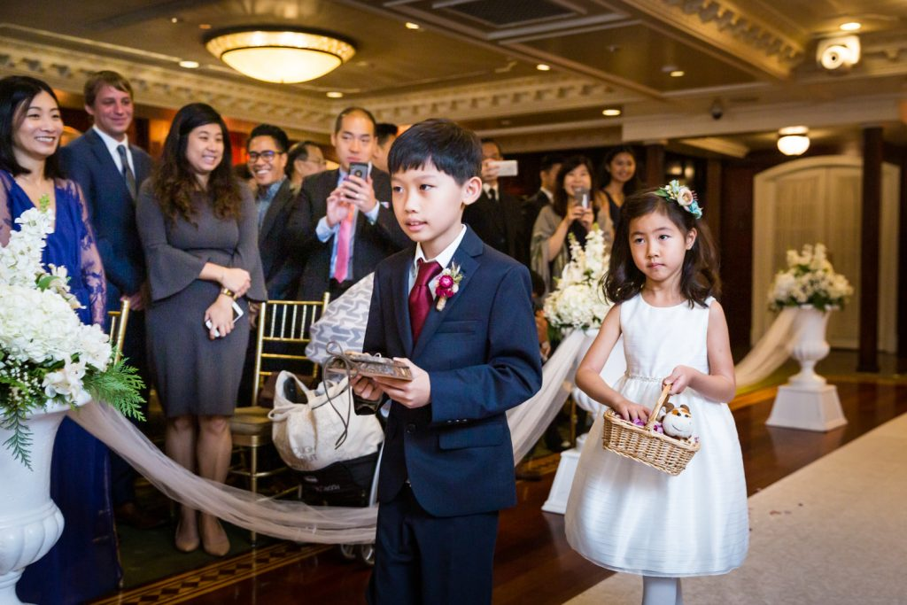 Little flower girl and ring bearer walking down aisle at a Westbury Manor wedding