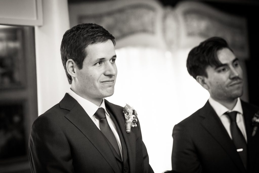 Black and white photo of groom waiting for bride at ceremony