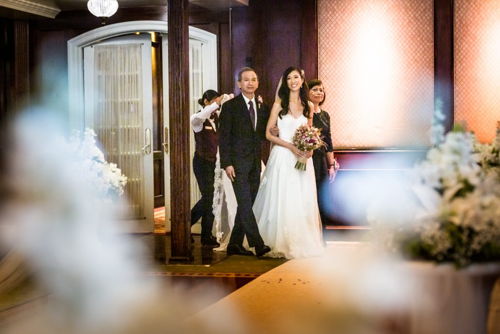 Bride escorted by both parents walking down aisle at a Westbury Manor wedding