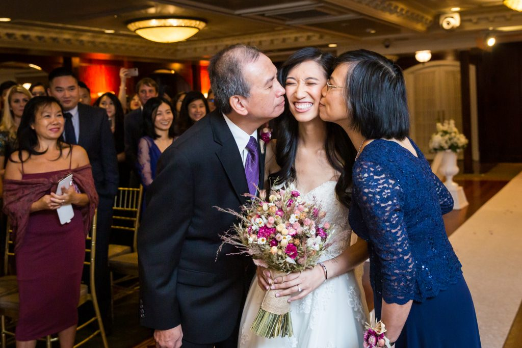 Bride being kissed on both cheeks during ceremony at a Westbury Manor wedding