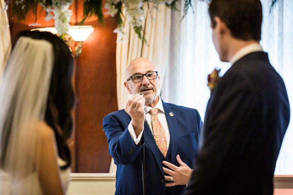 Officiant holding up wedding ring during ceremony