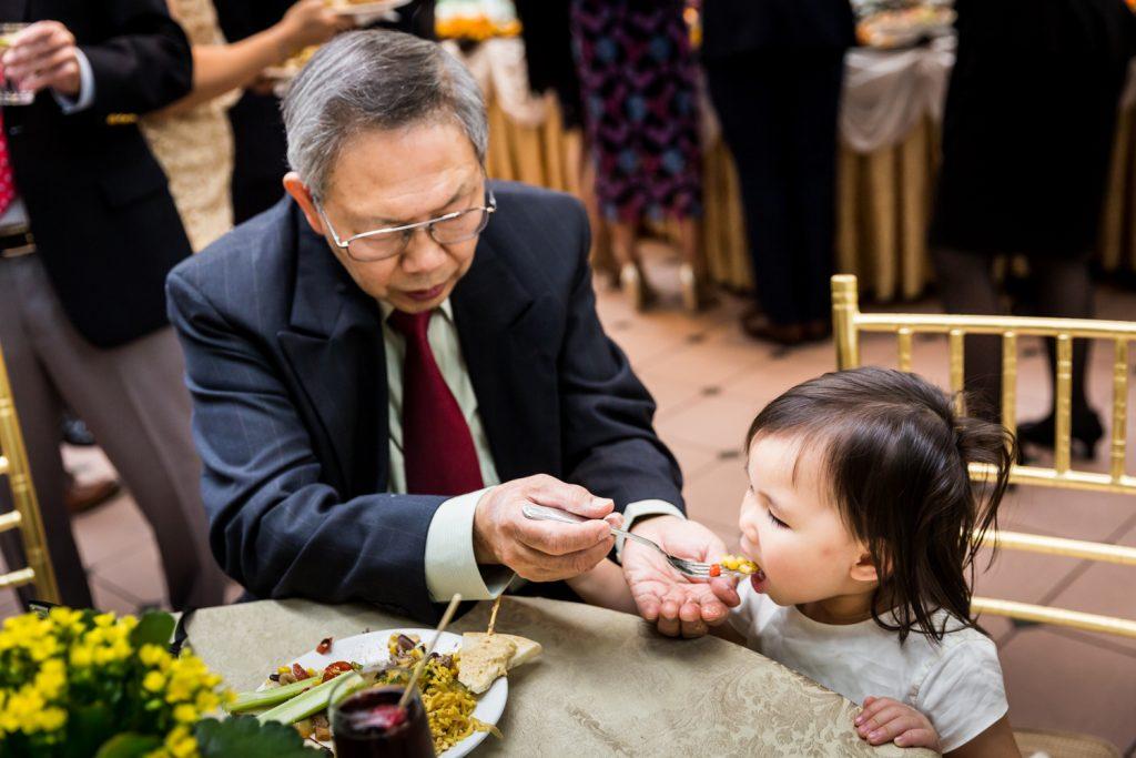 Older man feeding corn to a little girl