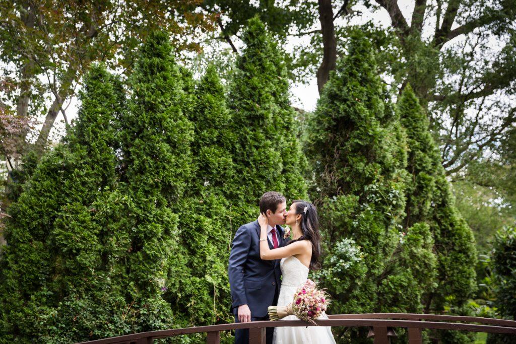 Bride and groom kissing on bridge in garden at a Westbury Manor wedding