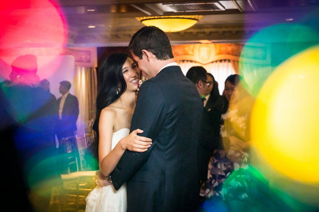 Bride and groom at first dance with multi colored lights