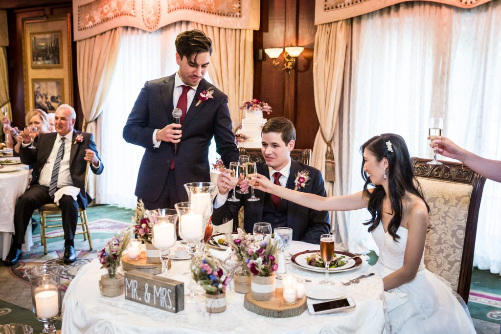 Best man toasting glasses with bride and groom