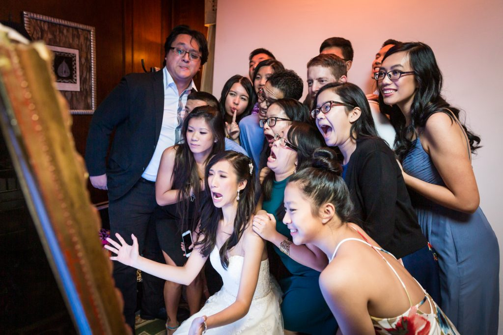 Bride and large group of guests taking photo at photo booth at a Westbury Manor wedding