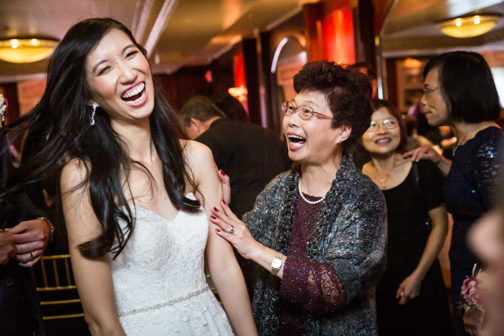 Bride and older woman laughing at reception at a Westbury Manor wedding
