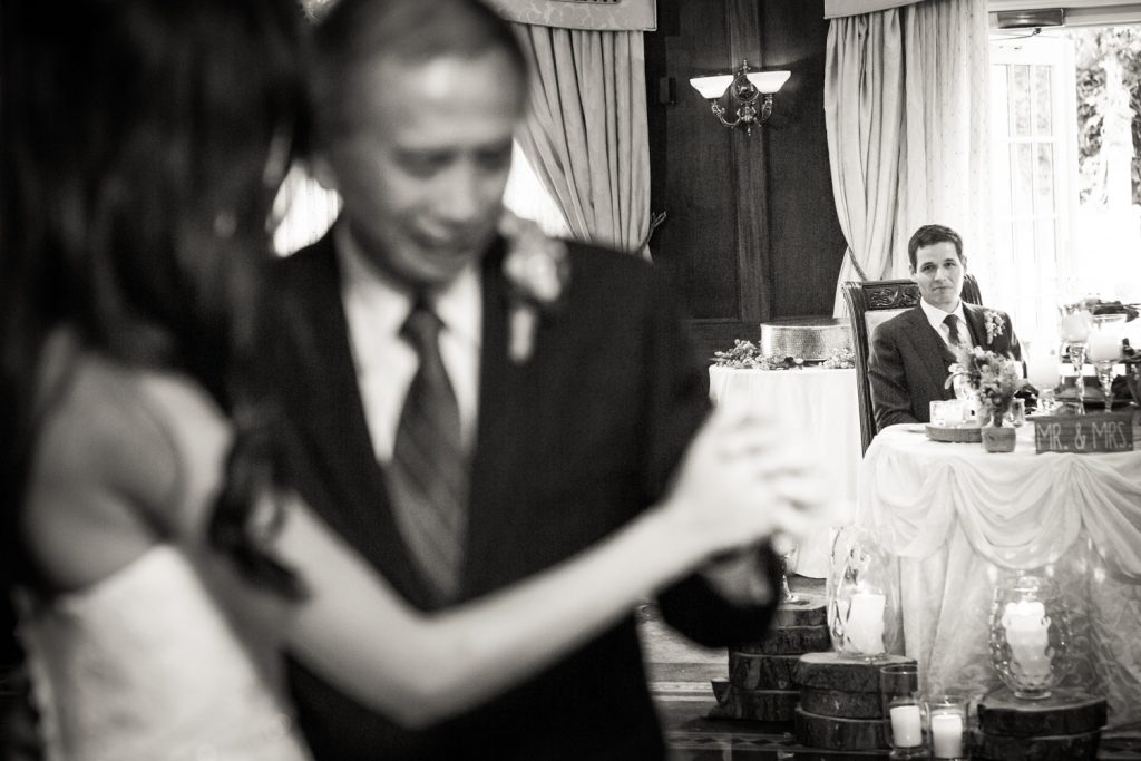 Black and white photo of groom watching bride dance with father