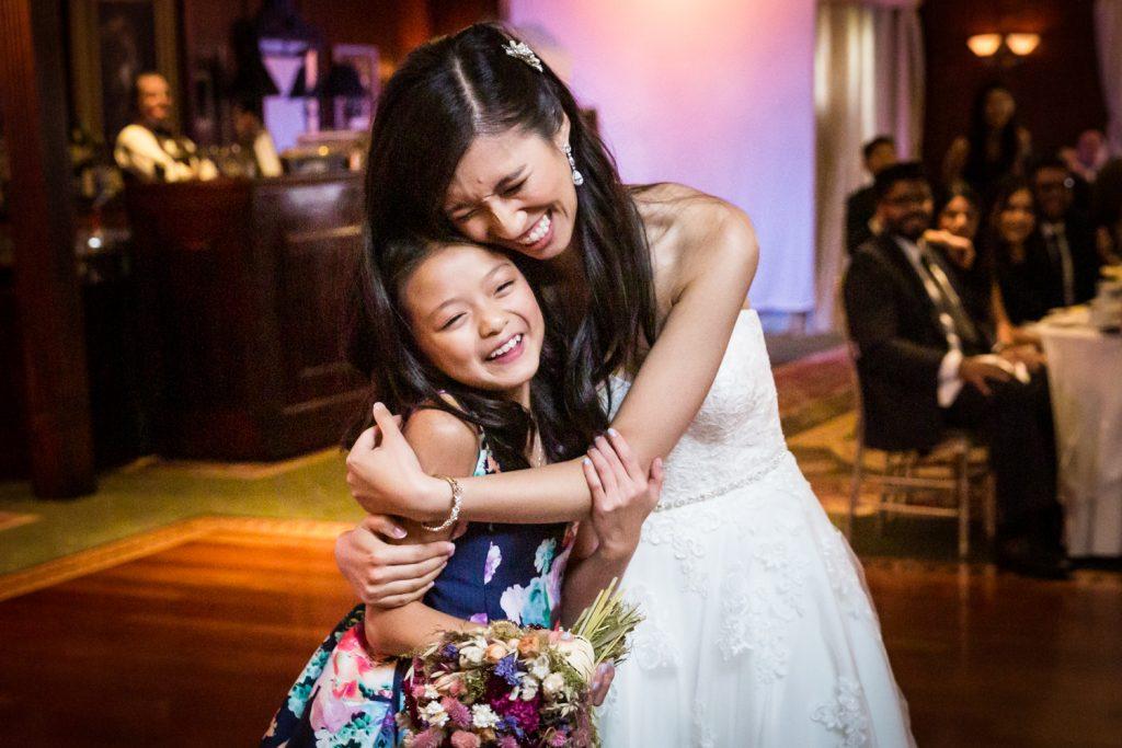 Bride hugging little girl holding bridal bouquet