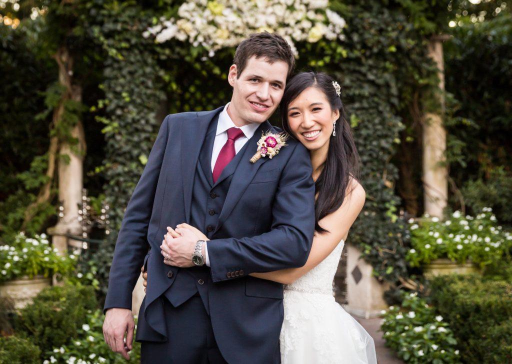 Portrait of bride and groom hugging in garden at a Westbury Manor wedding