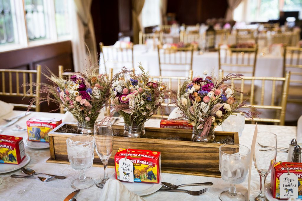 Table setting with dried flower bouquets in wooden trough at a Westbury Manor wedding