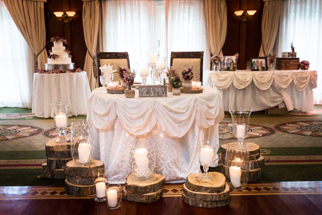 Three tables with wood pillars and candles at a Westbury Manor wedding