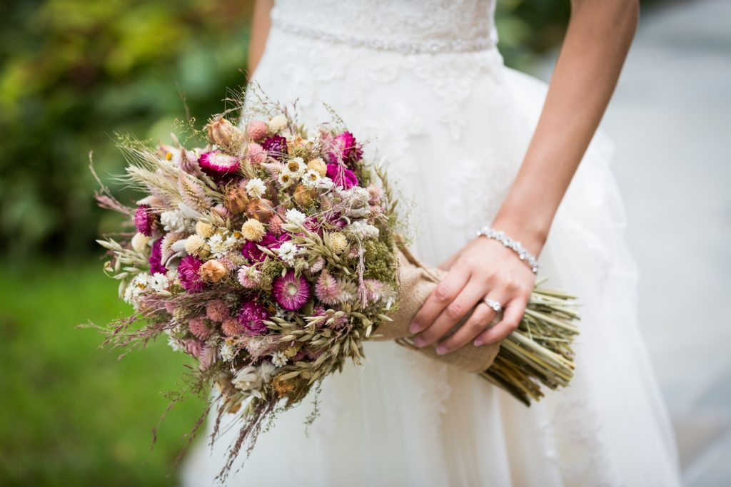 Close up on bride holding dried flower bouquet at a Westbury Manor wedding
