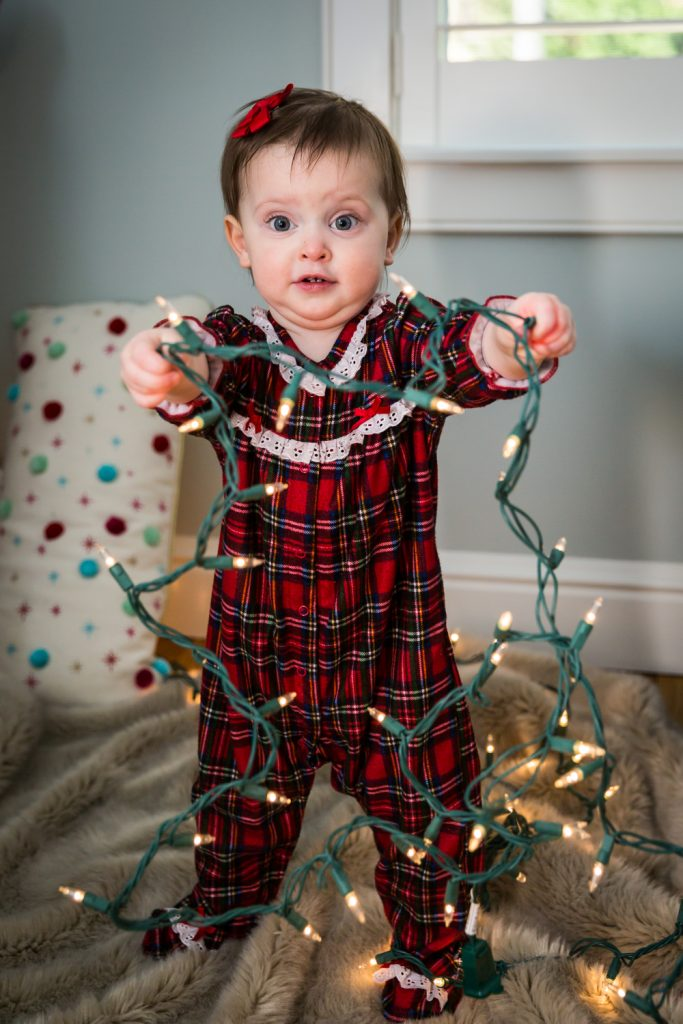 Child holding Christmas lights for article on how to get your kids to look into the camera