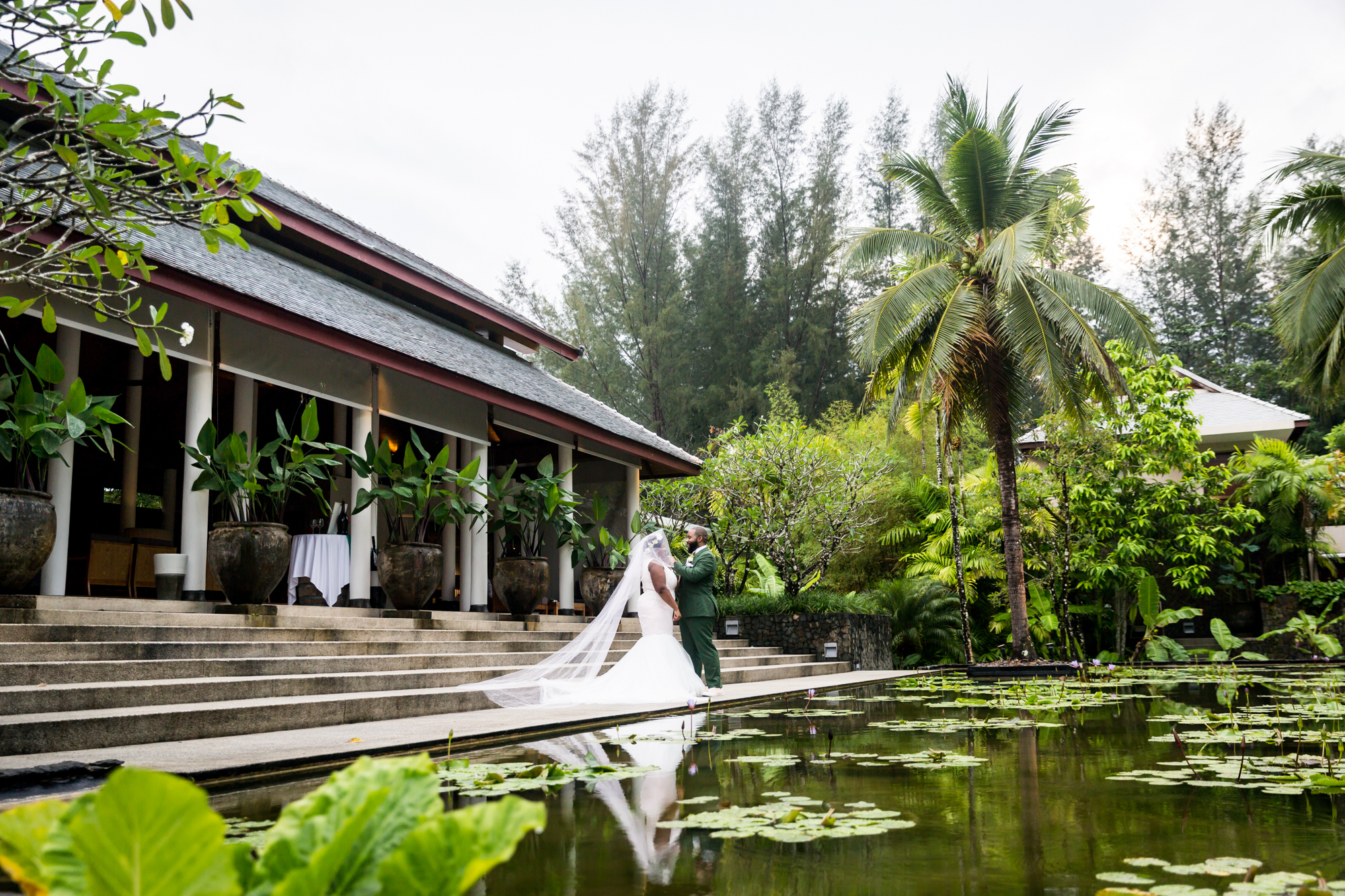 Bride and groom in front of pond for an article on destination wedding photography tips