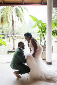 Groom adjusting bride's dress for an article on destination wedding planning tips