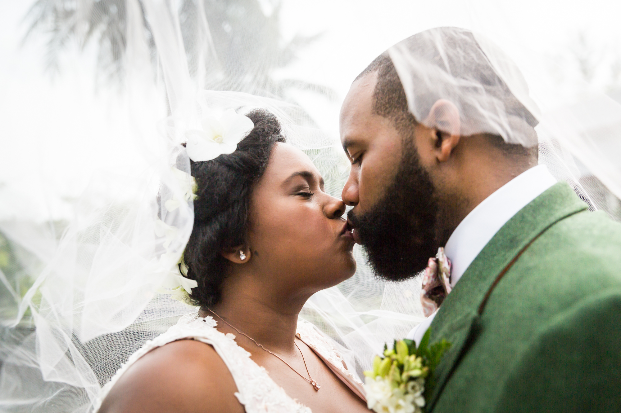 Bride and groom kissing under veil for an article on destination wedding planning tips