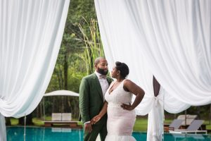 Bride and groom posed by pool for an article on destination wedding planning tips