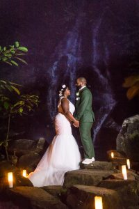 Bride and groom by waterfall for an article on destination wedding planning tips