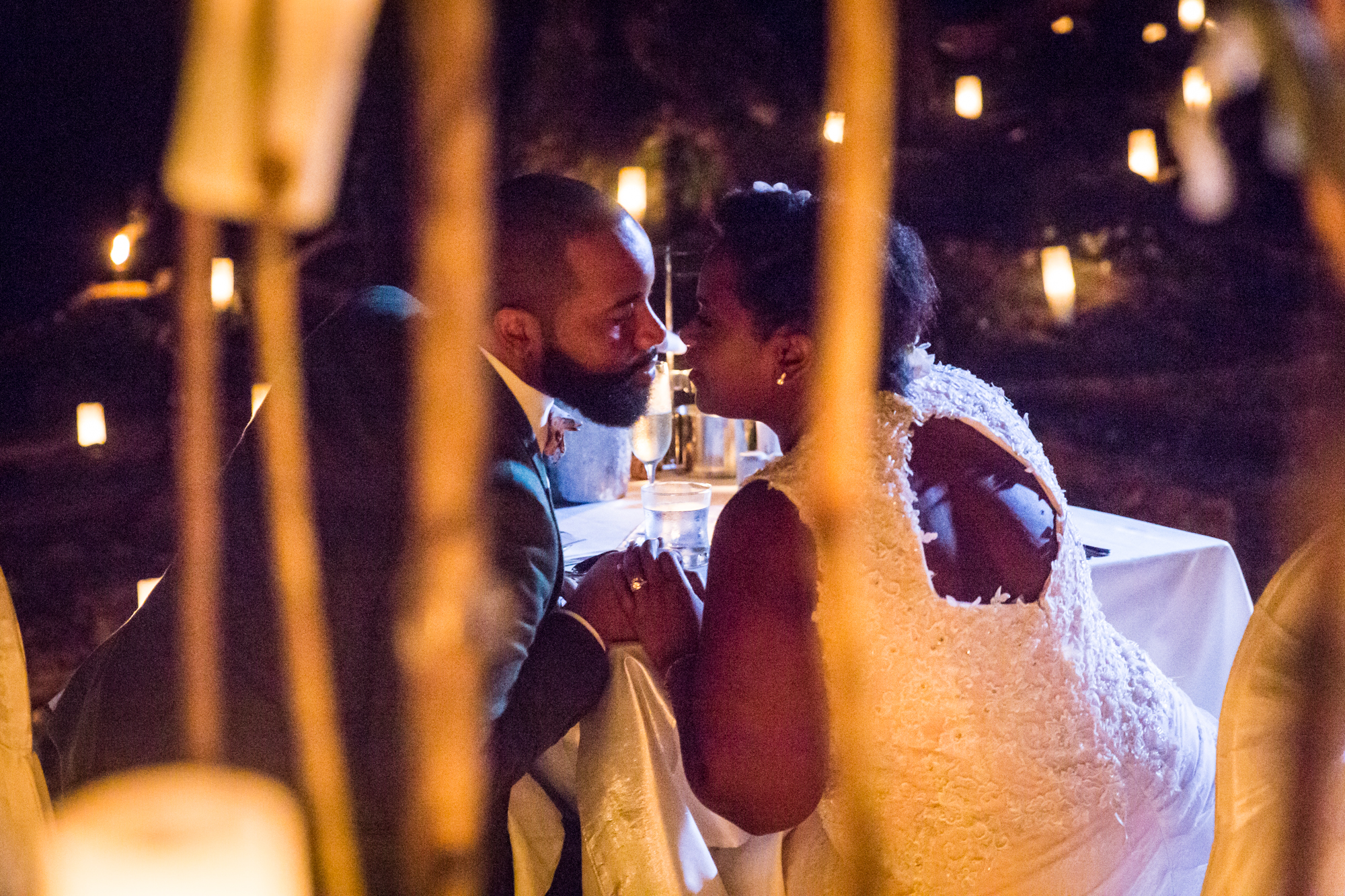 Bride and groom kissing by candlelight for an article on destination wedding planning tips