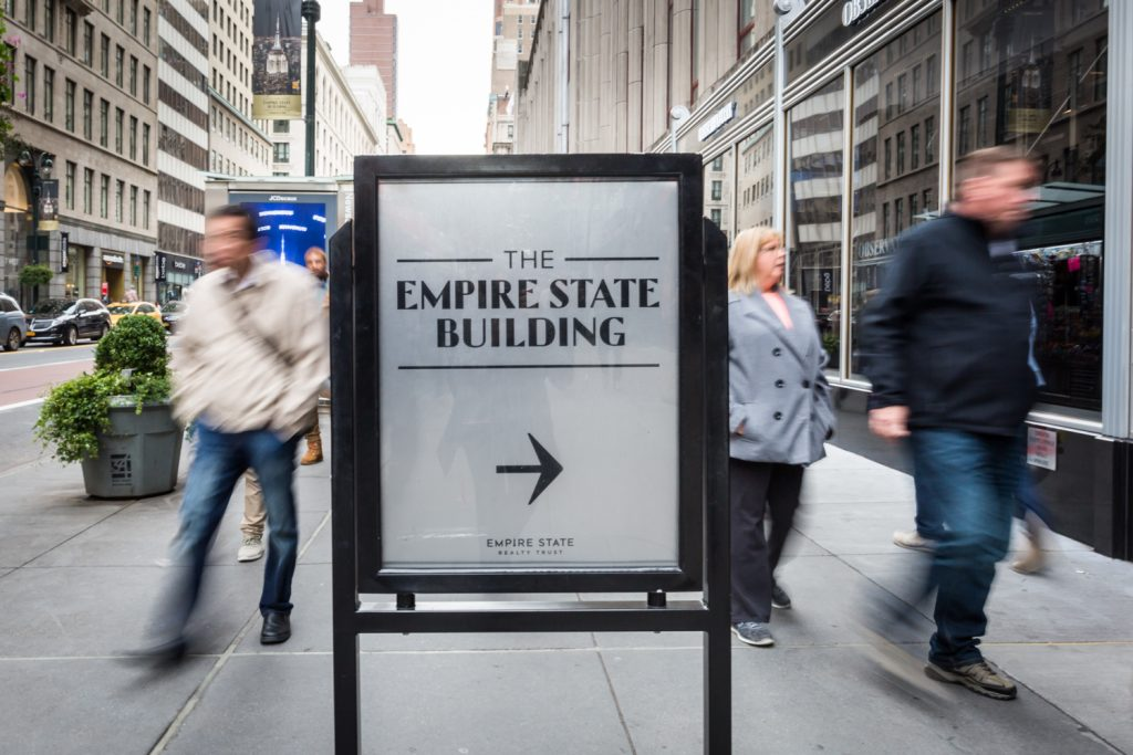 Empire State Building sign with people rushing past in a blur for an article on how to propose on top of the Empire State Building