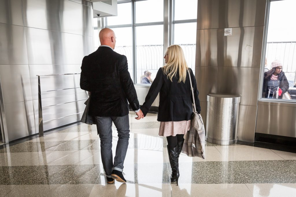 Couple holding hands and walking in lobby of Empire State Building for an article on how to propose on top of the Empire State Building