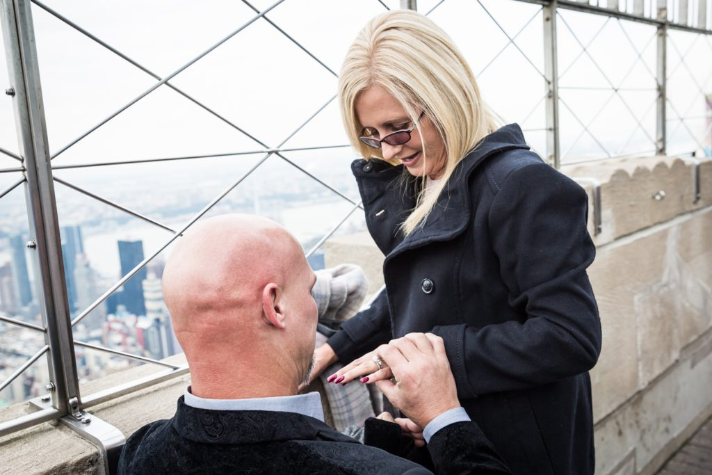 Man putting ring on woman's finger for an article on how to propose on top of the Empire State Building