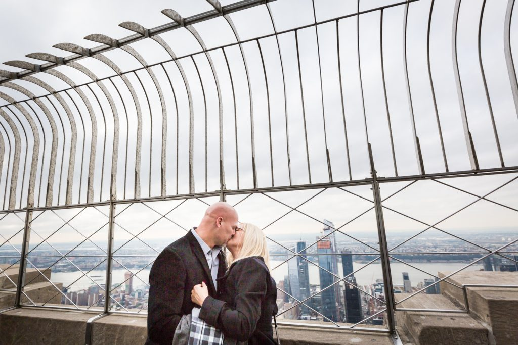 Couple kissing under fencing for an article on how to propose on top of the Empire State Building