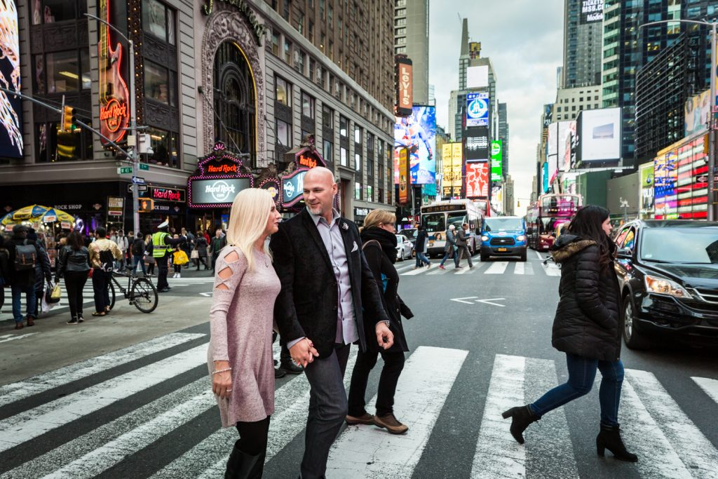 Couple walking in crosswalk through Times Square