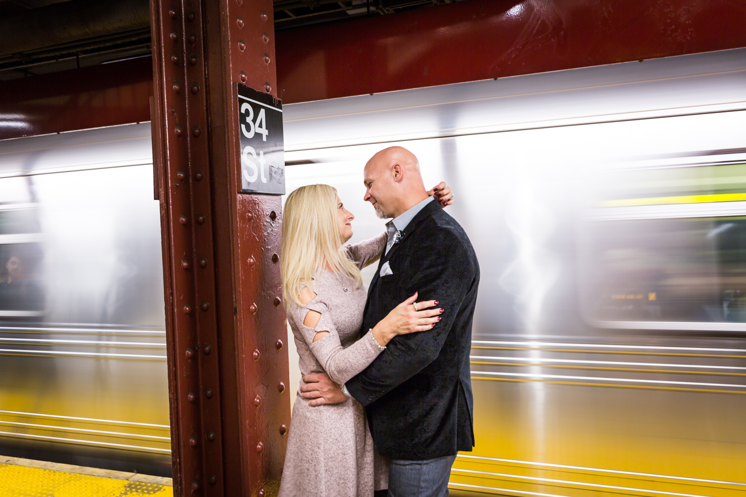 Couple hugging on platform while subway train is speeding past