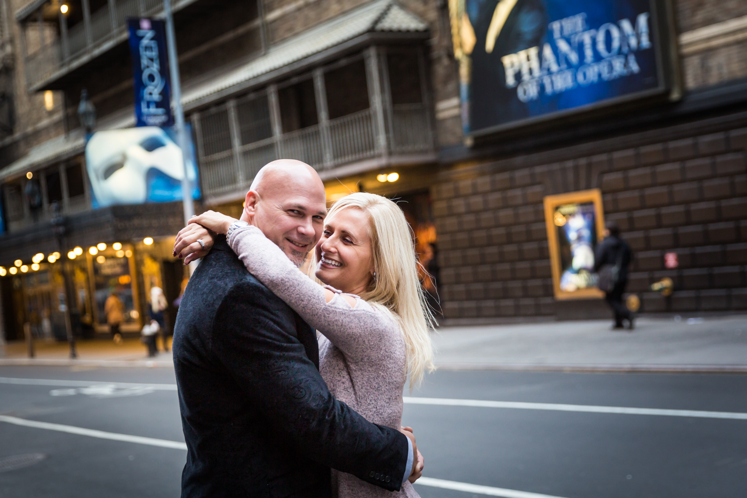 Couple hugging in front of Broadway theater for an article on how to propose on top of the Empire State Building
