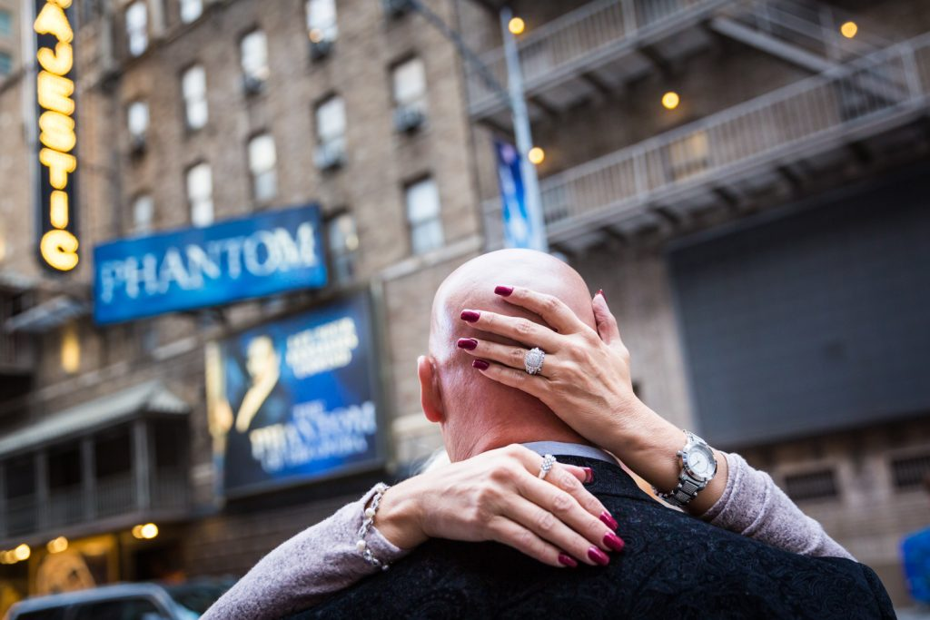 Close up on woman embracing bald man with hand on his head