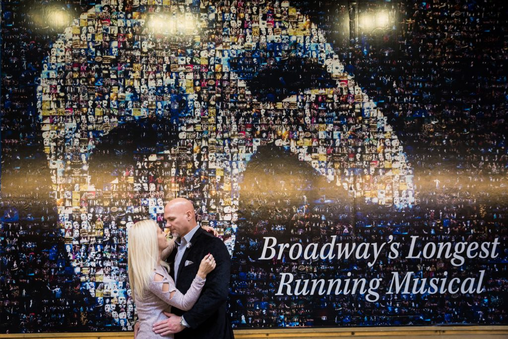 Couple hugging against wall advertisement for Phantom play