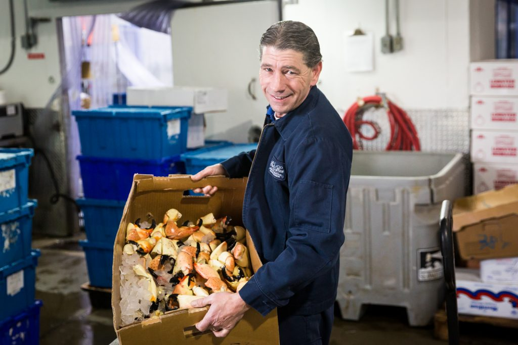 Man holding box of stone crab claws for an article on website photography tips