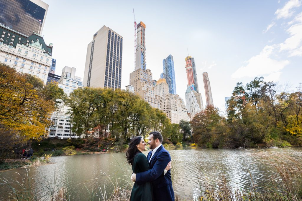 Couple hugging in Central Park with lake and NYC skyline in background for an article on winter portrait tips