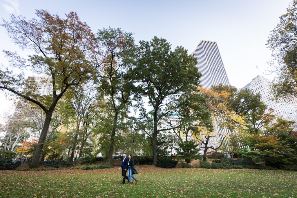 Man and woman walking through Central Park with NYC skyline in background
