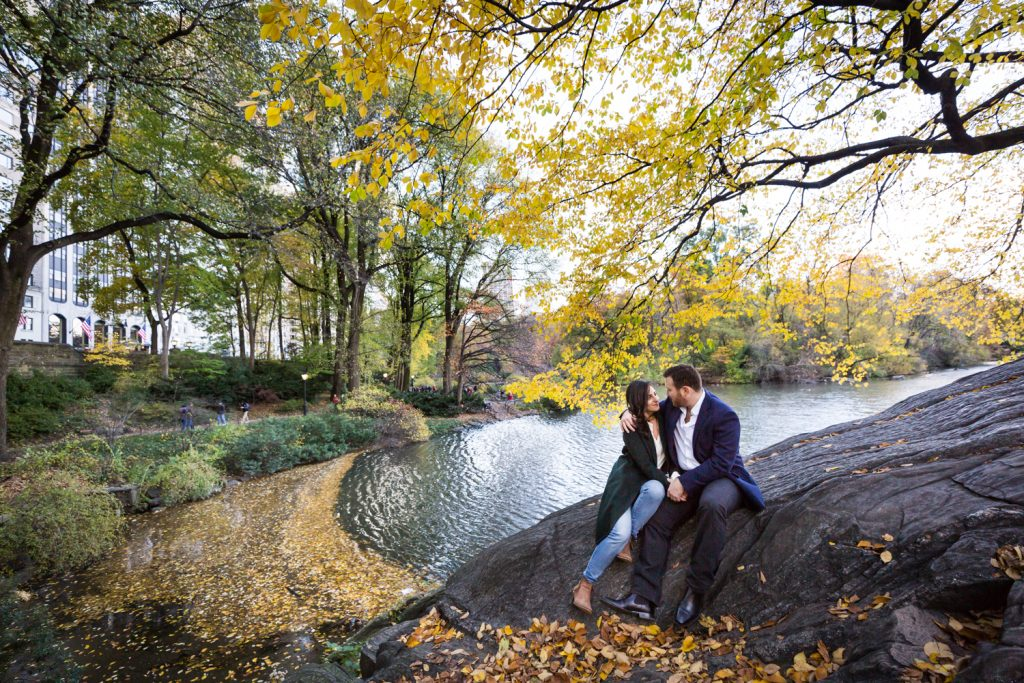 Couple sitting on a rock surrounded by yellow leaves for an article on winter portrait tips