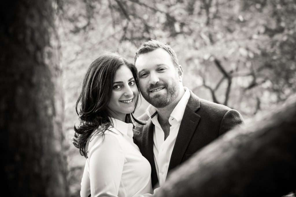 Black and white portrait of man and woman through branches in Central Park