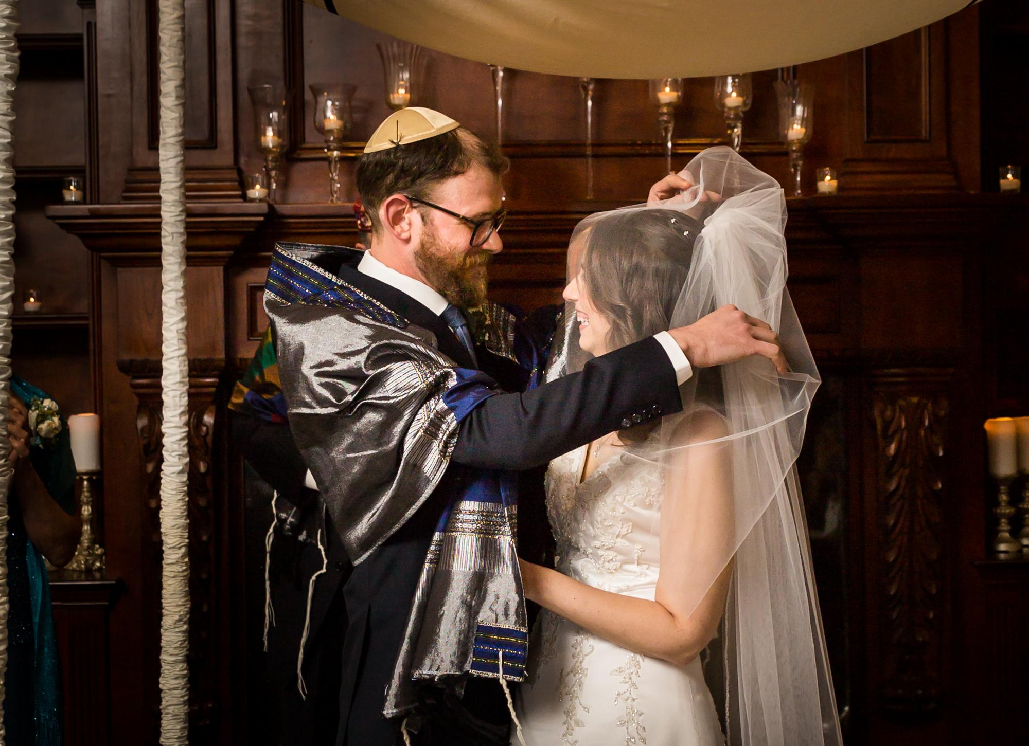 Groom lifting bride's veil for an article on band vs DJ