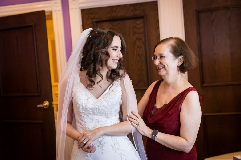 Bride turning around and laughing with her mother