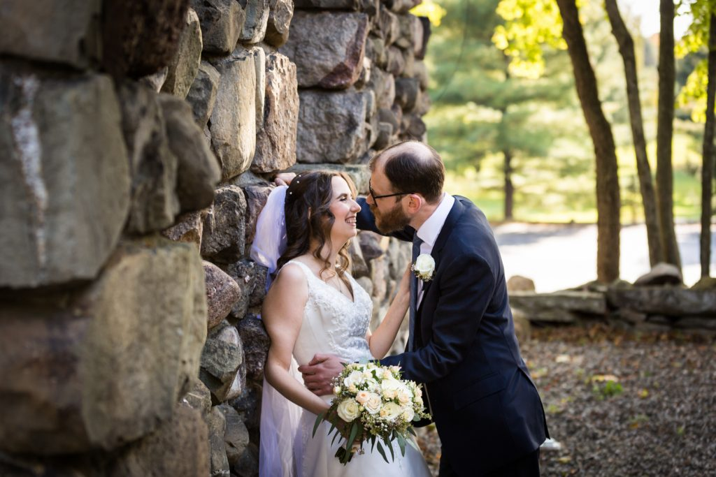Bride leaning against stone wall and laughing with groom