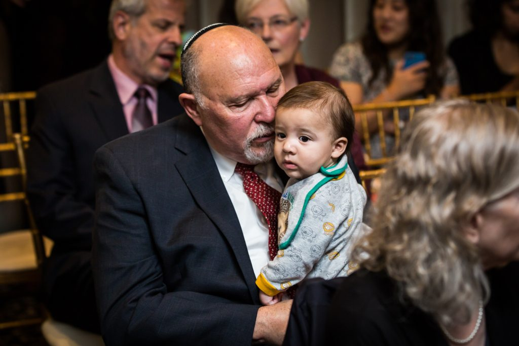 Grandfather holding little grandson at Jewish wedding ceremony